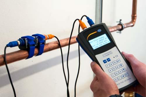 Il flussometro a ultrasuoni PCE-TDS 100 mentre effettua una misura in una tubatura